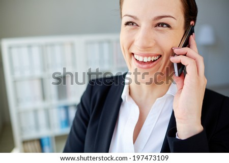 Young and pretty employee speaking on cellphone