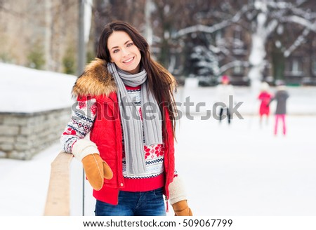 Young and pretty girl skating on outdoor open air ice-rink at winter.