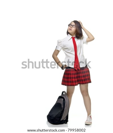 Young and pretty teenager school girl poses with school bag, isolated background