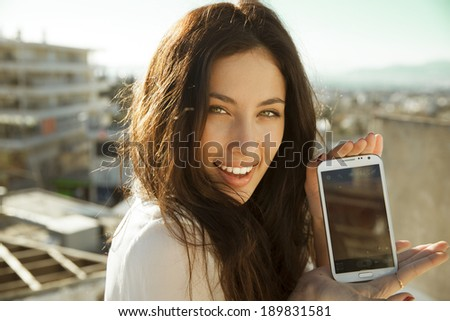 Young and pretty woman holding her smartphone. outdoors shot. vertical - stock photo