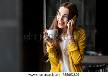 Young and pretty woman in yellow sweater using phone holding a cup of coffee in the dark cafe interior - stock photo
