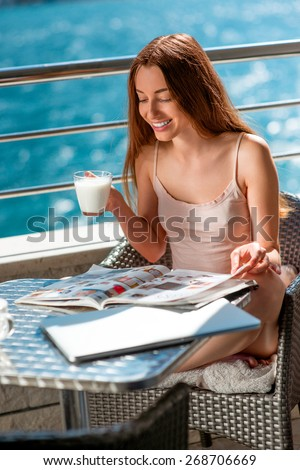 Young and pretty woman reading magazine and drinking milk on the balcony near the sea. Good morning concept - stock photo