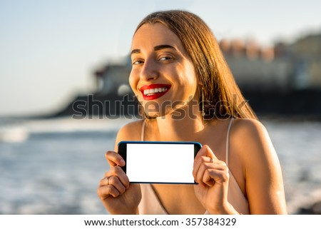 Young and pretty woman showing smartphone with white screen outside on the beautiful rocky seacoast - stock photo