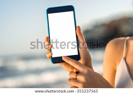 Young and pretty woman showing smartphone with white screen outside on the seacoast background. Close-up view - stock photo