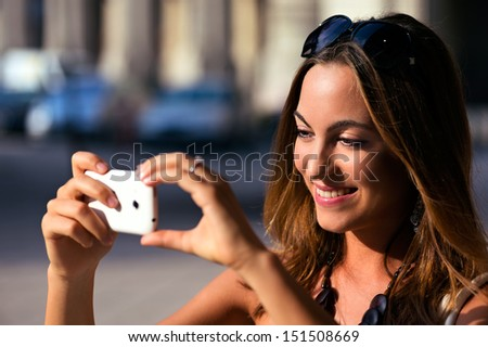 Young and pretty Woman taking photo with her smartphone while sightseeing - stock photo