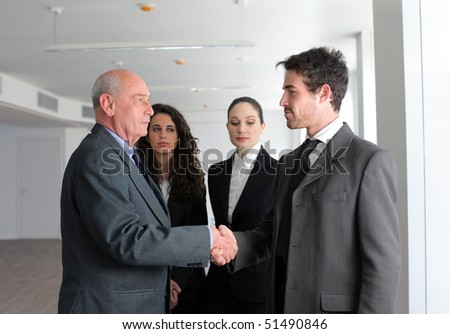 Young and senior businessmen shaking hands with businesswomen on the background - stock photo