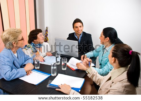 Young and senior people having a business meeting in an office and sitting around table making conversation  and laughing - stock photo