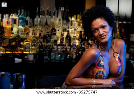 Young  and sexy bartender in a nightclub bar. - stock photo