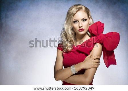 young and sexy beautiful blond woman in red dress with nice hair style and a big bow on shoulder.looking in camera  - stock photo