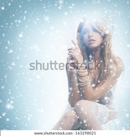 Young and sexy redhead woman in white lingerie over the winter background with the snow - stock photo