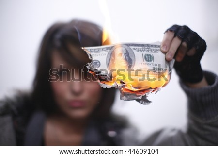 Young and sexy woman burning hundred dollar bills. - stock photo