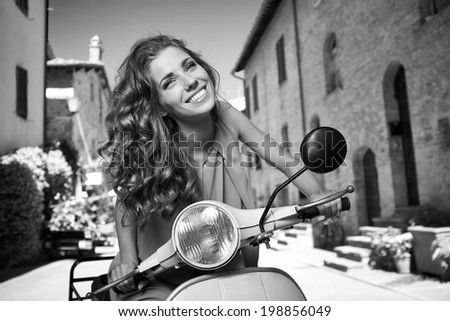 Young and sexy woman with her motor scooter. BW photo - stock photo