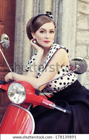 Young and sexy woman with her motor scooter - retro style image. - stock photo