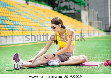 Young and slim athlete runner stretches on the field.Workout - stock photo