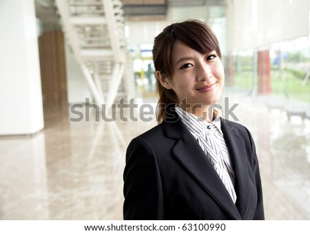 young and smiling business woman Standing in front of the office - stock photo