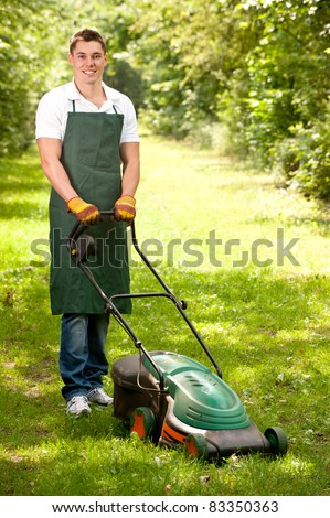Young and smiling gardener with lawnmover