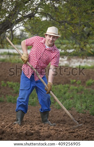 Young and smiling gardener with pitchfork