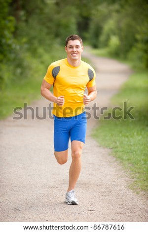 Young and smiling jogger  in the park - stock photo