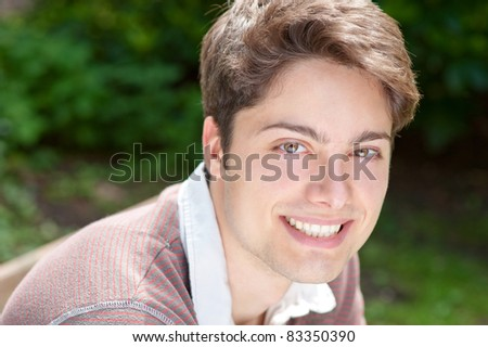 Young and smiling man in the park
