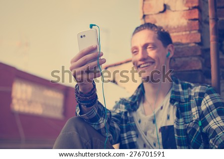 Young and smiling man on the roof, looking at mobile phone and listening music (intentional vintage color, focus on mobile phone) - stock photo
