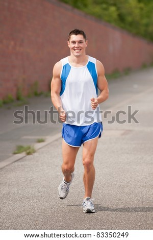 Young and smiling man running in the city