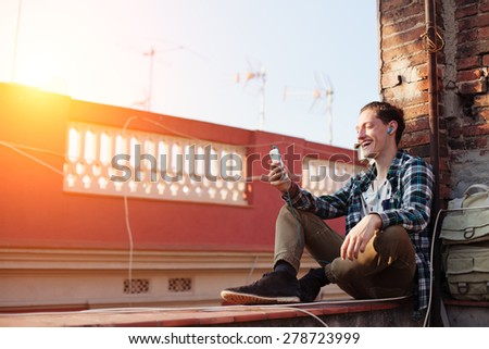 Young and smiling man sitting on the roof with mobile phone and listening music in earphones (intentional sun glare) - stock photo