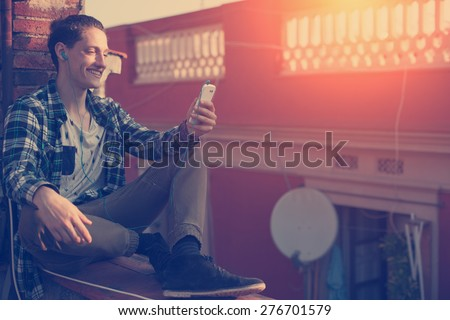 Young and smiling man sitting on the roof with mobile phone and listening music (intentional sun glare and vintage color, focus on mobile phone) - stock photo