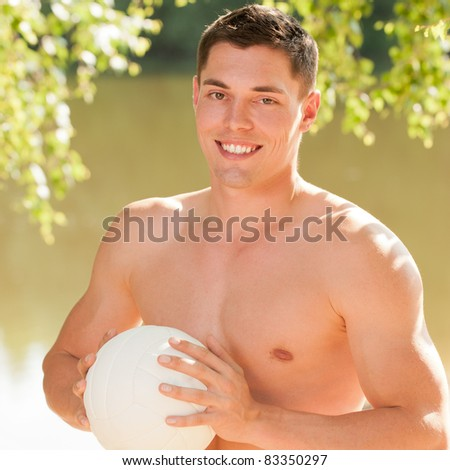 Young and smiling man with ball at the beach - stock photo