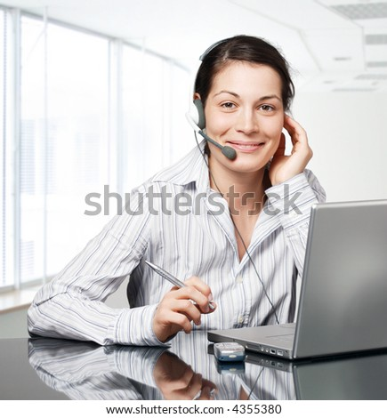 Young and smiling operator works on a laptom computer in a modern office. - stock photo