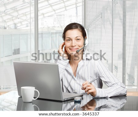 Young and smiling operator works on a laptop computer in a modern office. - stock photo
