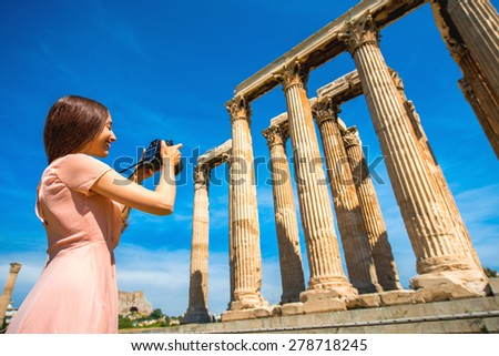 Young and smiling woman photographer taking picture with professional camera of Zeus temple in Acropolis - stock photo