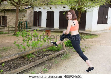 Young and smiling woman runner warm up outdoor