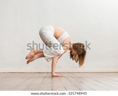 Young and sporty girl training in gym. Yoga exercise. - stock photo