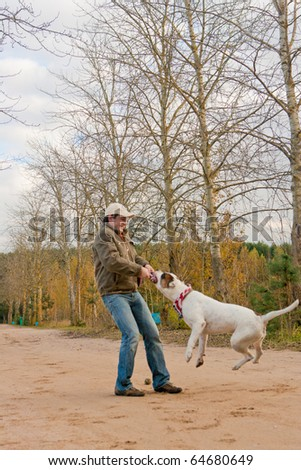 young and strong looking caucasian handsome man in cap and jeans with smile training his big bulldog dog using thick rope put into the dog's mouth and trying to rotate it, shoot made on location
