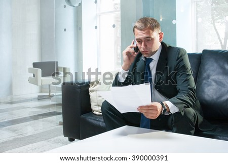 Young and successful businessman is reading documents and making a call - stock photo