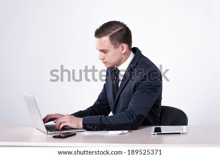 Young and successful businessman sitting at table and talking on a cell phone. Handsome man is sitting at laptop working on the tablet. Confident businessman smiling  in formal wear writing on paper