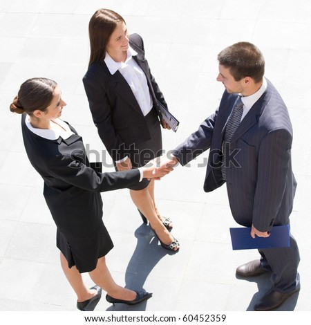 Young and successful businesspeople shake hands - stock photo