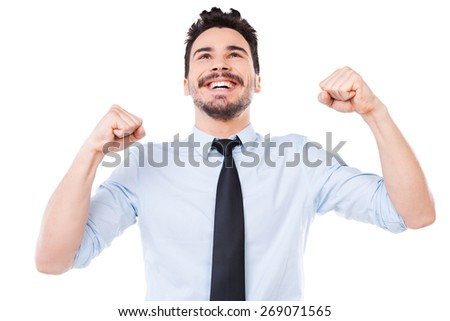 Young and successful. Happy young man in shirt and tie keeping arms raised and smiling while standing against white background - stock photo