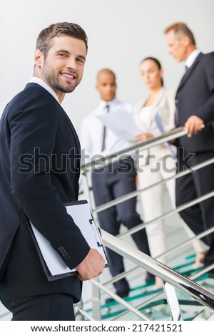 Young and successful. Low angle view of confident young man in formalwear looking over shoulder and smiling while moving up by staircase with people in the background  - stock photo