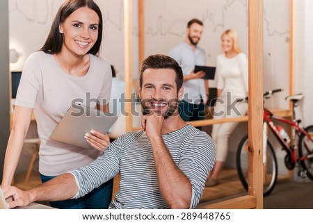 Young and successful team. Cheerful young man and woman looking at camera and smiling while their colleagues working in the background - stock photo