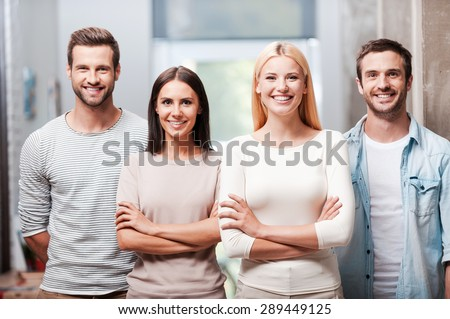 Young and successful team. Four young business people in smart casual wear standing close to each other and smiling discussing  - stock photo