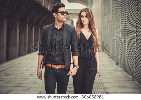 Young and trendy man and woman models walks of the modern street. Fashion Style - stock photo