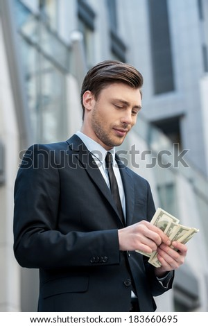 Young and wealthy. Confident young man in shirt and tie counting money and while standing outdoors