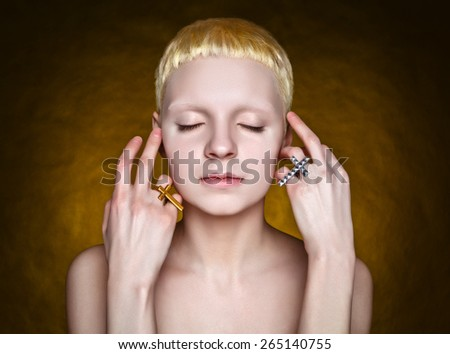 young androgynous girl with white hair in the studio on yellow  textured background - stock photo