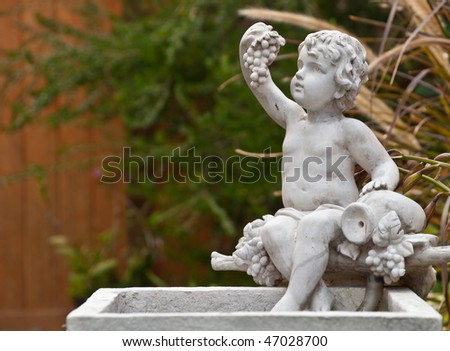 Young Angel Sculpture Fountain in Garden - stock photo