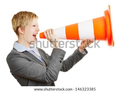 Young angry business woman screaming in a traffic cone