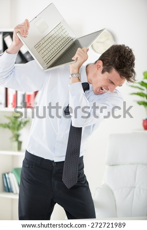 Young angry Businessman standing in the office and holding a laptop as if to wants break it. - stock photo