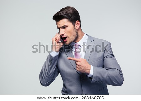 Young angry businessman talking on the phone over gray background