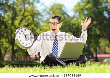 Young angry businessperson with laptop sitting on green grass and looking at clock in a park - stock photo