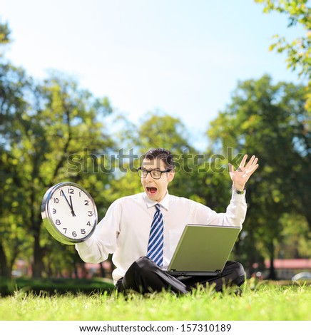 Young angry businessperson with laptop sitting on green grass and looking at clock in a park, shot with a tilt and shift lens - stock photo